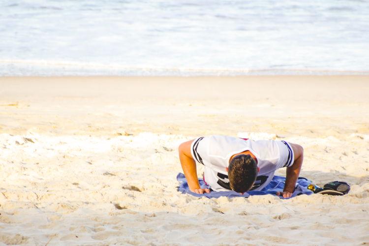 Young Man Exercising At Beach