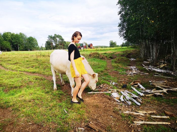 Girl standing with cow on field