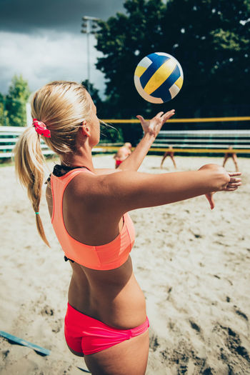 Rear View Of Bikini Woman Playing Beach Volleyball