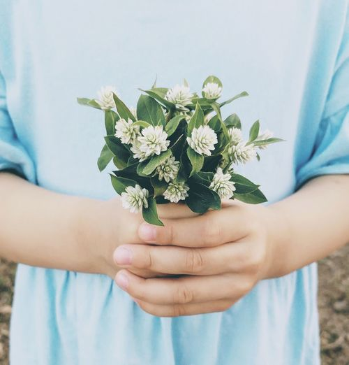 Midsection of woman holding bouquet of flowers