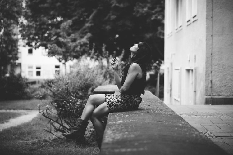 Full Length Of Woman Sitting On Retaining Wall
