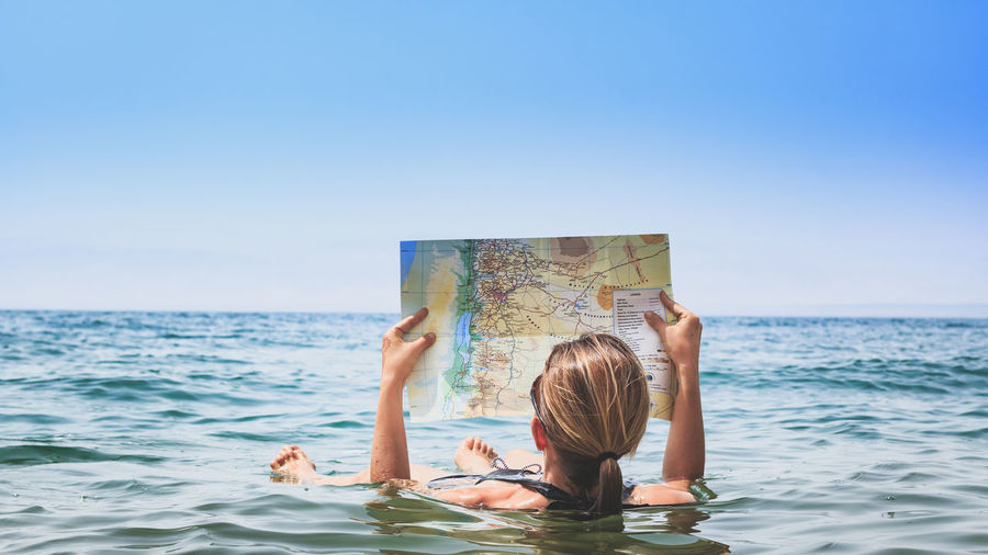 Full Length Of Woman Holding Map While Swimming In Dead Sea