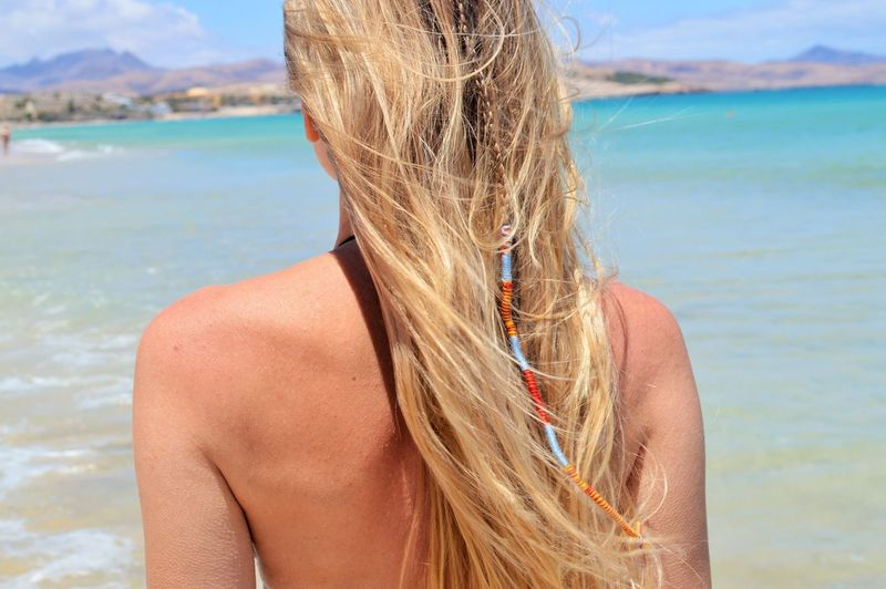 Rear View Of Mature Woman With Blond Hair Standing Against Sea