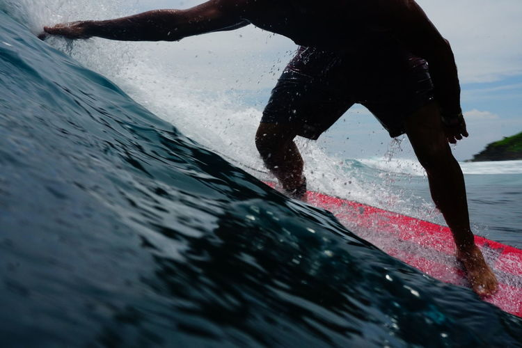 Low section of surfer in sea