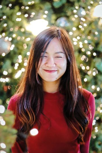 Smiling young woman standing against christmas tree