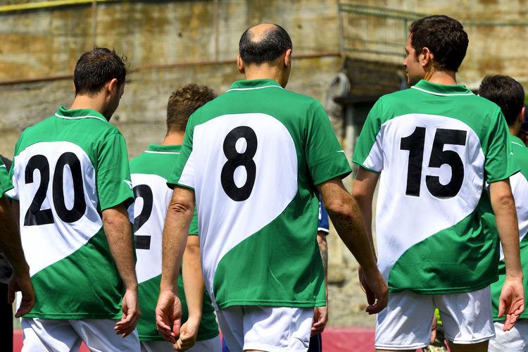 Rear view of men standing on soccer field