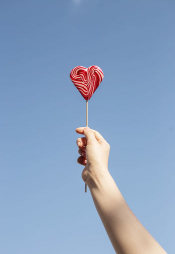 Midsection of person holding heart shape against blue sky