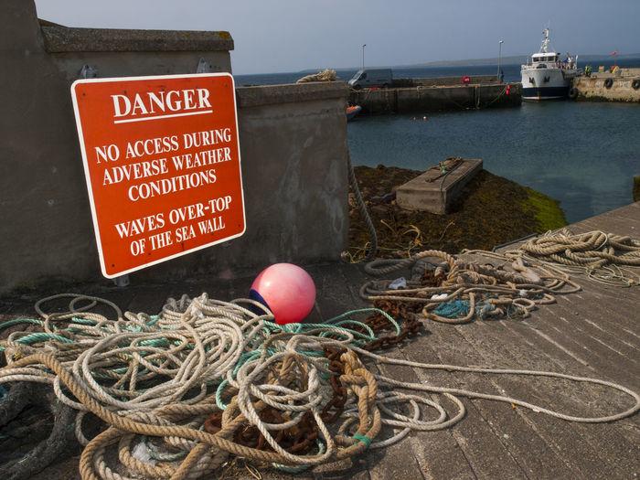 Ropes by warning sign at harbor