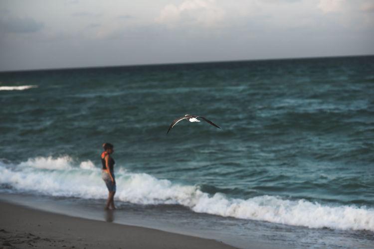 Full length of woman flying over beach against sky