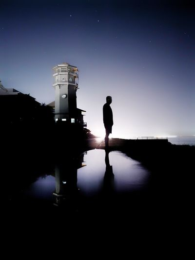 Silhouette man standing against clear sky at night