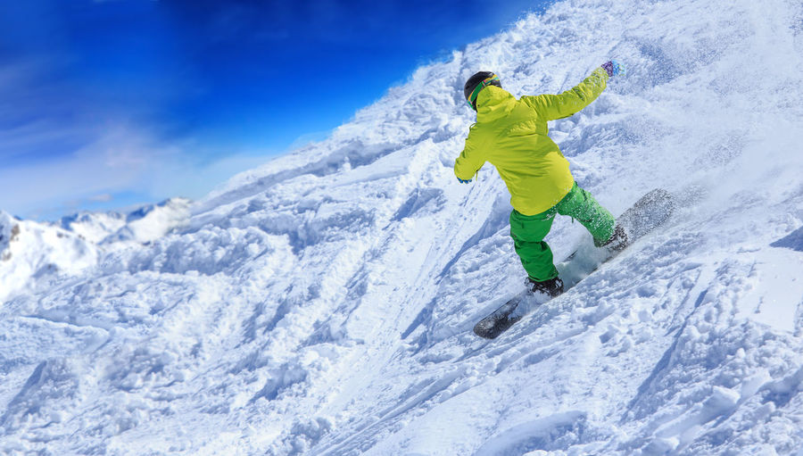 Rear View Of Young Man Skiing On Snowcapped Mountain Against Sky