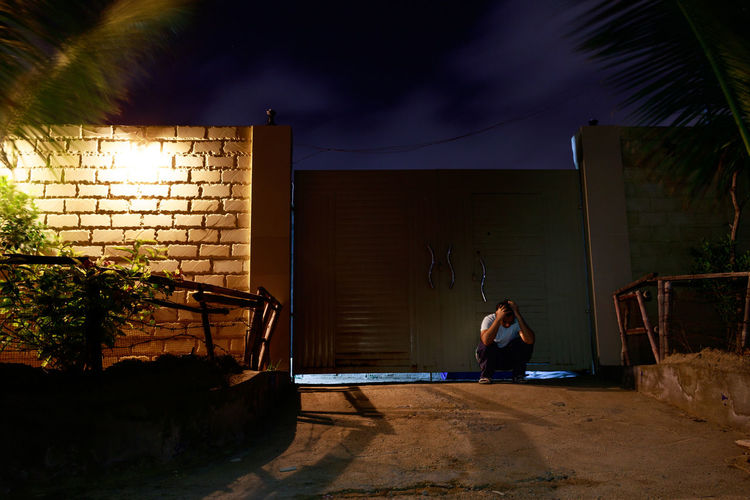 Boy in house against sky at night