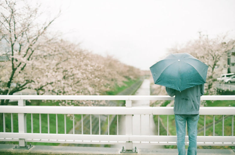 Man With Umbrella Standing On Bridge Over River Against Sky