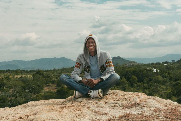 Full length of man sitting on mountain against sky