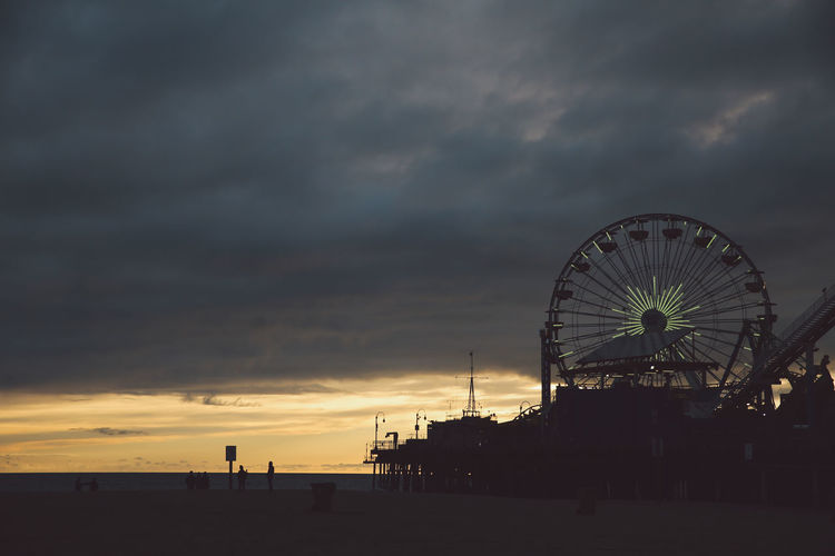 Silhouette Santa Monica Pier And Ferris Wheel At Beach Against Cloudy Sky During Sunset