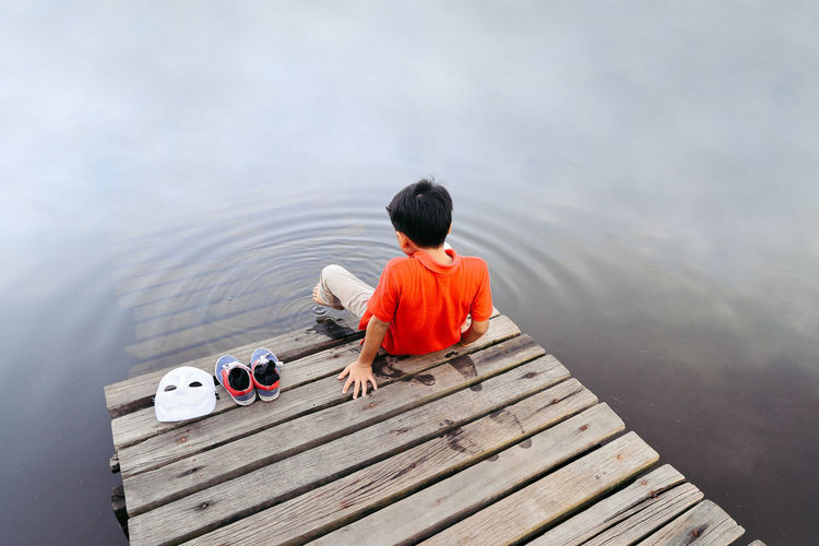 Rear view of boy sitting by lake on jetty