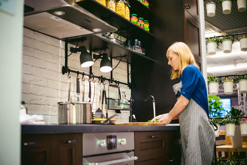 Side view of woman washing food at kitchen sink