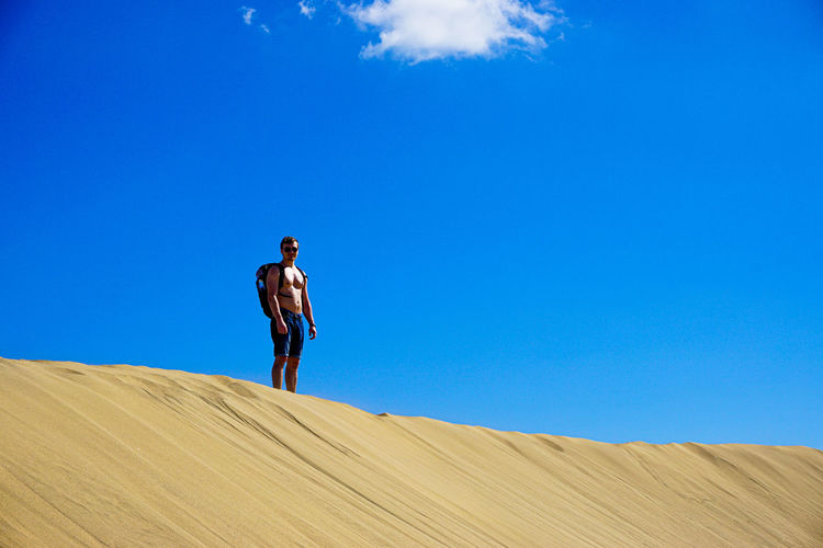 Shirtless man standing on sand against blue sky