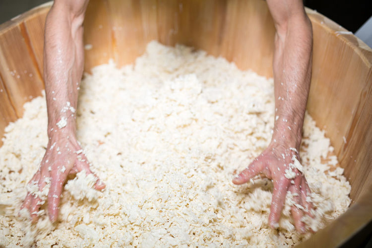 High angle view of worker mixing mozzarella cheese in wooden container at factory