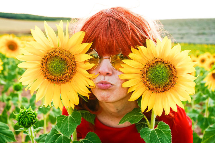 Close-up woman by of sunflower on field