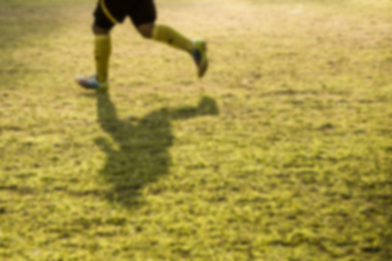 Vague Abstract Sports Fitness Game Football Team Background Soccer One Person Real People Lifestyles Land Shadow Human Body Part Nature Low Section Day Field Body Part Green Color Leisure Activity Human Leg Unrecognizable Person Plant Grass Sport Sunlight Outdoors Human Limb Focus On Shadow Effort
