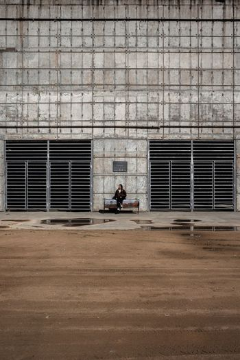 Woman sitting on bench against building