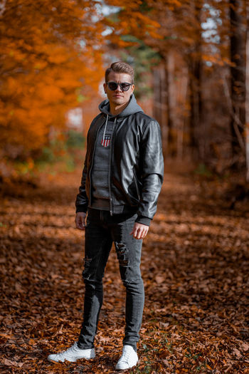 Portrait of young man wearing sunglasses standing on street during autumn