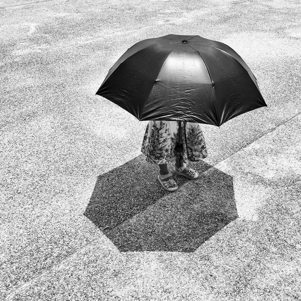 Hiding from the sun Umbrella Protection Under One Person Day Below Summer Real People Outdoors People