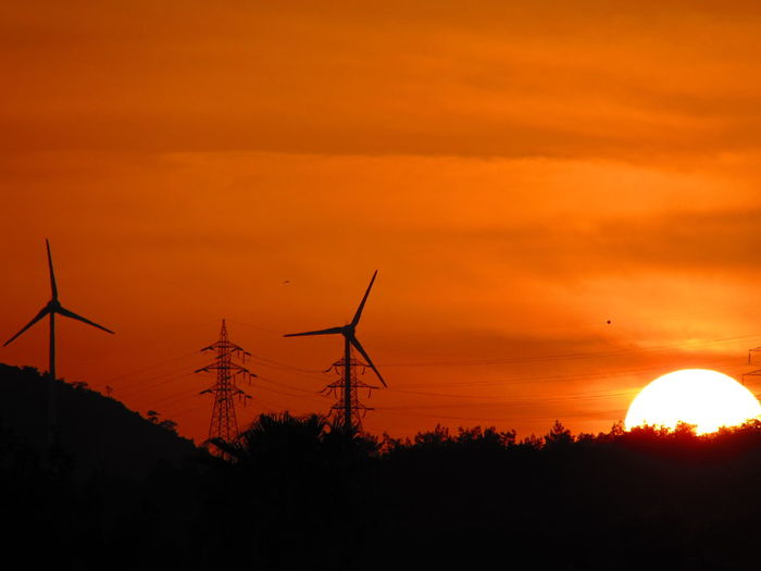 Silhouette Wind Turbines And Trees Against Orange Sky During Sunset