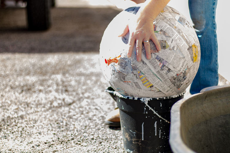 Cropped image of hand touching papier mache ball on bucket