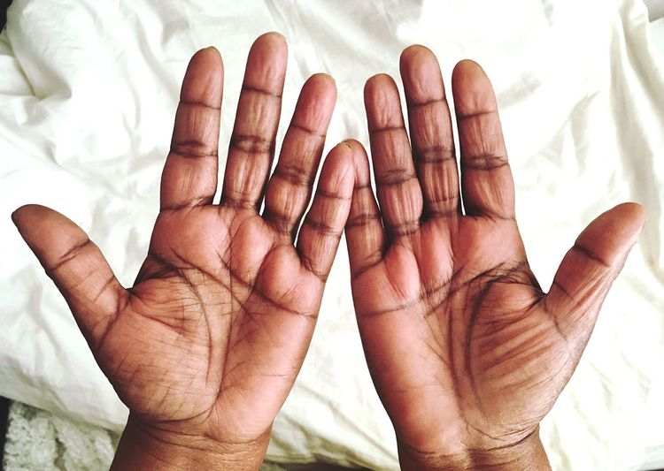 Cropped Hands Of Person On White Sheet