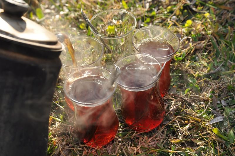 High angle view of teapot pouring turkish tea in cup on field