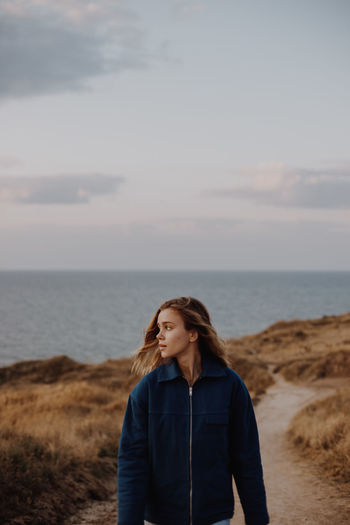 Young woman walking on dirt road against sea and sky
