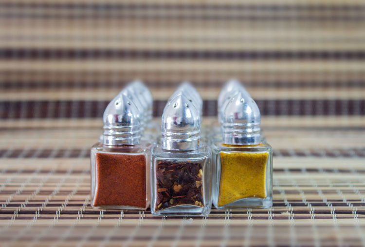 Close-Up Of Spices Arranged In Glass Containers On Mat