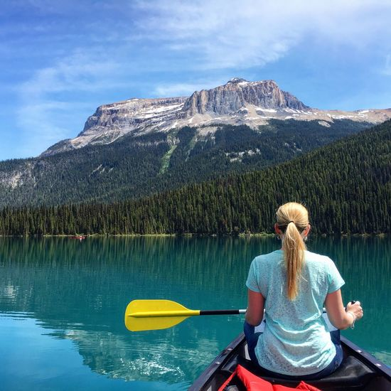 Rear View Of Woman Sitting On Canoe In Lake Against Mountain
