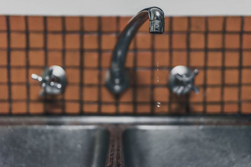 Close-up of drops dripping from faucet in bathroom