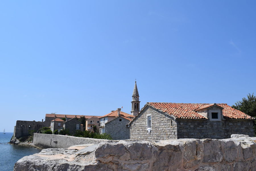 Budva,Montenegro Architecture Belief Blue Budva Old Town Building Building Exterior Built Structure Clear Sky Copy Space Day History House Montenegro Nature No People Outdoors Place Of Worship Religion Roof Tile Sky Spirituality Stone Wall The Past Travel Destinations