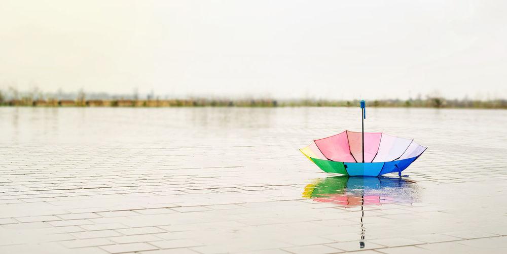 Multi colored umbrella on lake against sky
