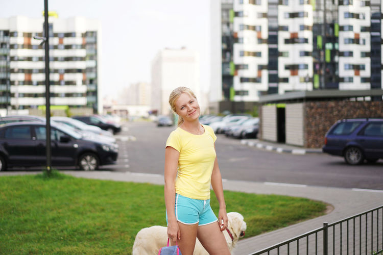 Portrait Of Young Woman Standing With Labrador Retriever On Footpath
