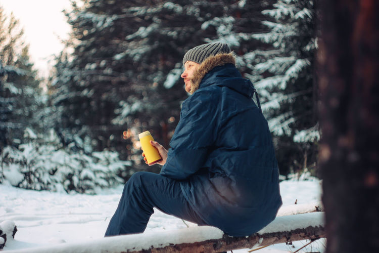 Side View Of Man Having Drink While Sitting Against Trees During Winter