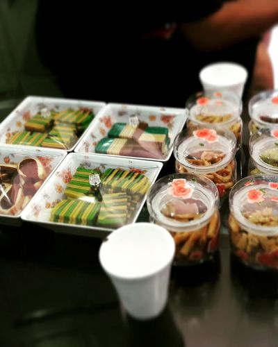 High angle view of cakes and cookies in containers on table