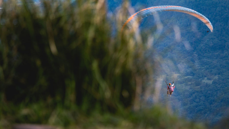 Person paragliding against blurred background