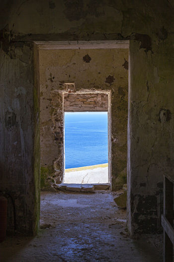 View of old building by sea against sky seen through window