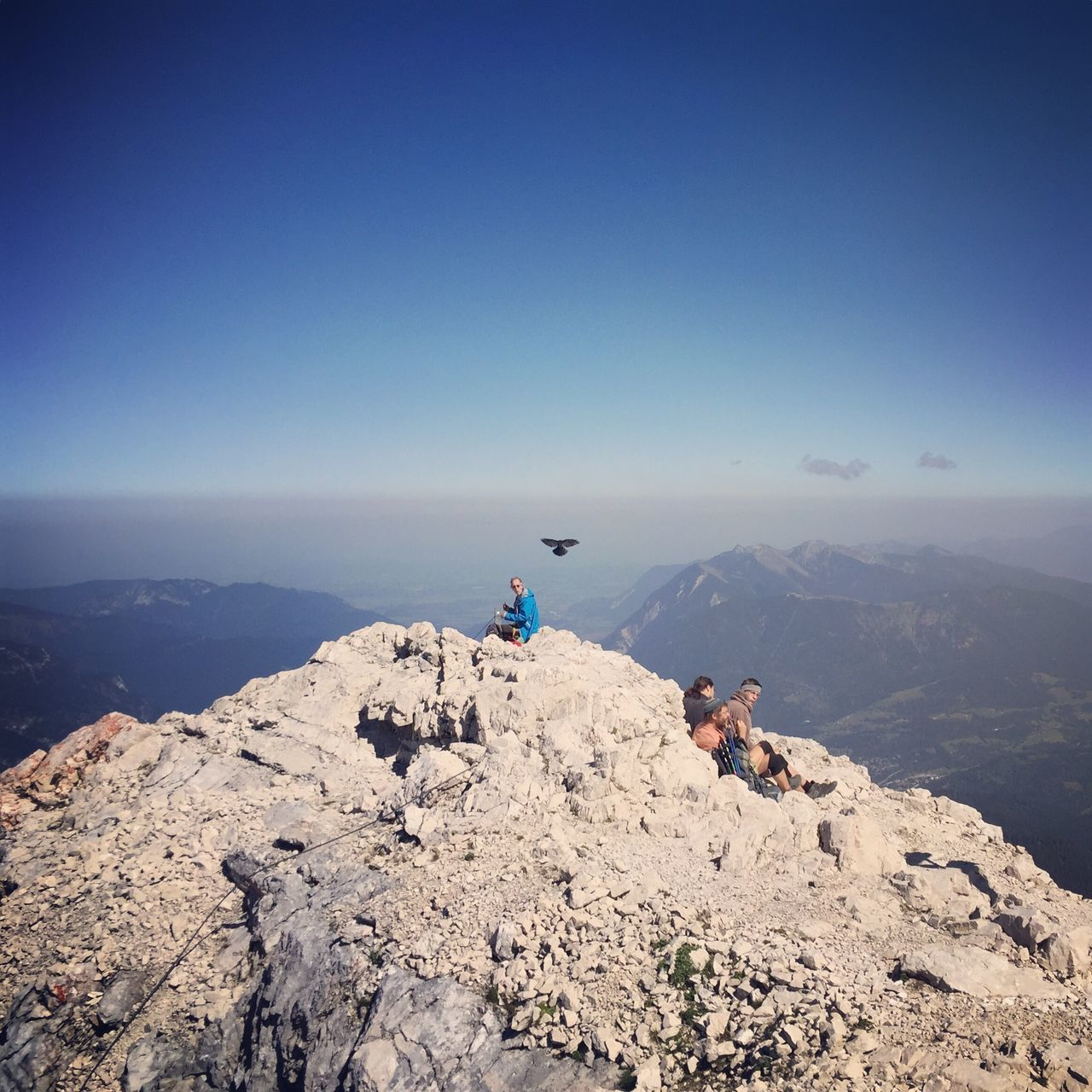real people, adventure, nature, lifestyles, leisure activity, mountain, clear sky, rock - object, day, scenics, men, beauty in nature, tranquility, outdoors, full length, extreme sports, blue, one person, landscape, friendship, sky, people