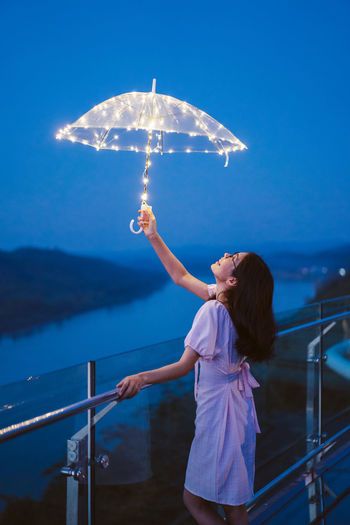 Young woman holding illuminated umbrella standing by railing during dusk