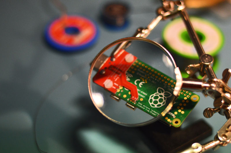 High angle view of magnifying glass and computer chip