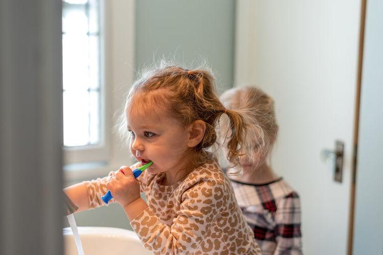 Cute girl brushing teeth at home