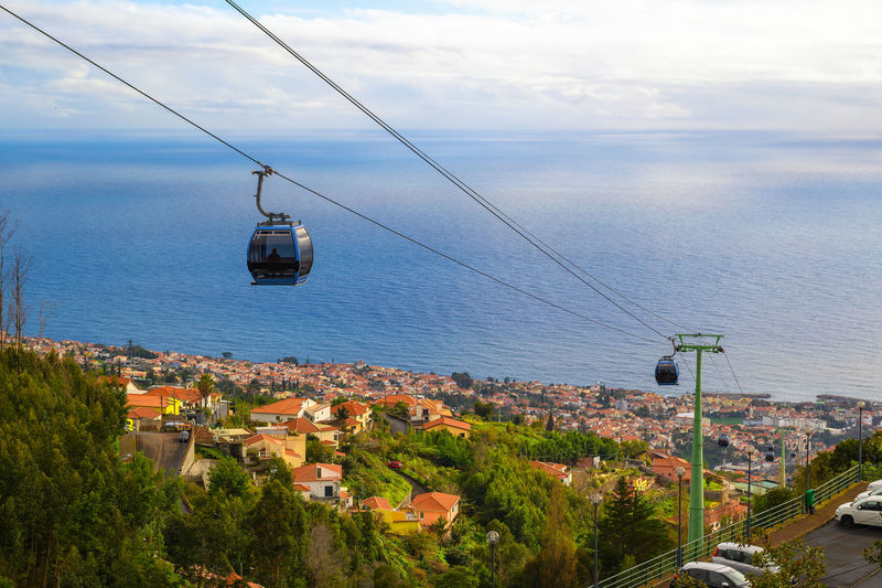 Overhead cable car over sea and buildings against sky
