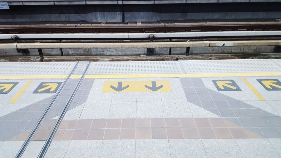 High Angle View Of Arrow Symbol On Railroad Station Platform