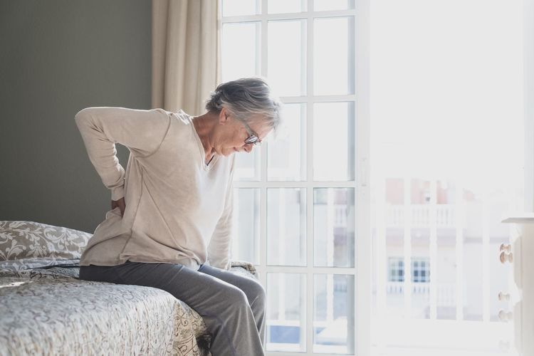 Midsection of man sitting by window